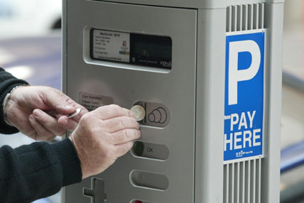 a person putting change in a parking meter
