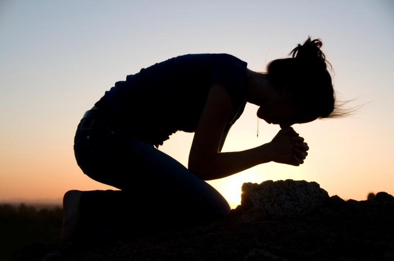 a woman praying at sunset