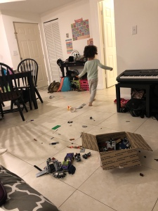 A toddler girl with a curly fro in pajamas walking out of a room with a floor covered in legos.